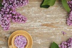 Belle tasse de fleurs lilas sur un vieux conseil texturisé Image stock