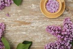 Belle tasse de fleurs lilas sur un vieux conseil texturisé Images stock