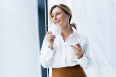 belle tasse de participation de femme d'affaires de café de sourire photos stock