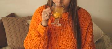 Belle tasse heureuse de boissons de jeune femme de thé d'argousier Dans le lit dans un portrait orange lumineux de plan rapproché photo stock