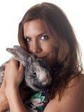 Belle tenuta e coccole castane sorridenti il suo coniglietto Immagini Stock