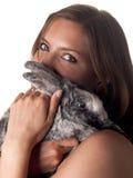 Belle tenuta e coccole castane sorridenti il suo coniglietto Fotografie Stock