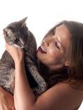 Belle tenuta e coccole castane sorridenti il suo gatto grigio sveglio Fotografia Stock