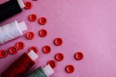 Belle texture avec un bon nombre de boutons rouges ronds pour la couture, la couture et les écheveaux des bobines du fil Copiez l photographie stock