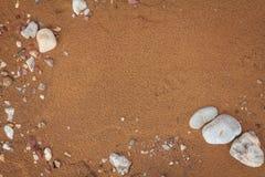 Belle texture de sable de plage avec des pierres Plage d'or d'été photographie stock libre de droits