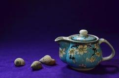 Belle théière bleue sur le plancher violet image libre de droits