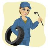 Belle travailleuse active dans le service des réparations de voiture tenant la clé de pneu et de roue Photo stock
