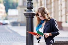 Belle étudiante dans le livre de lecture en verre Photos stock
