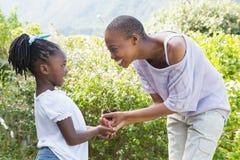 Belle usine de mère de sourire heureuse une fleur avec sa fille Image libre de droits