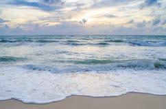 Belle vague sur la plage au coucher du soleil Photo stock