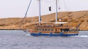 Belle vele turistiche dell'yacht nel mare tempestoso sui precedenti delle rocce Egypt video d archivio