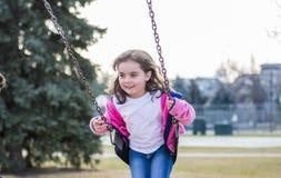 Belle vieille fille de cinq ans balançant dehors sur un terrain de jeu Photographie stock libre de droits