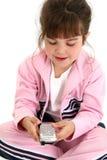 Belle vieille fille de cinq ans dans des vêtements roses de séance d'entraînement avec Cellph Photo libre de droits
