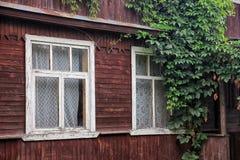 Belle vieille maison en bois de village de planche avec la crique blanche de fenêtres Photos stock