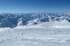 Belle viste dei picchi di montagna e della cresta Gli Snowboarders scendono il pendio fuori dalla strada immagine stock