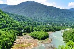 Belle viste delle montagne di Caucaso e di piccolo villaggio sulle banche del fiume Fotografie Stock