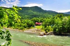 Belle viste delle montagne di Caucaso e di piccolo villaggio sulle banche del fiume fotografia stock