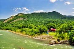 Belle viste delle montagne di Caucaso e di piccolo villaggio sulle banche del fiume immagine stock