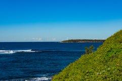 Belle vue d'océan avec la colline herbeuse verte et le ciel clair Image libre de droits