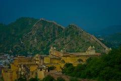 Belle vue de château jaune d'Amber Fort avec les arbres verts, les montagnes et les petites maisons près de Jaipur au Ràjasthàn Image libre de droits