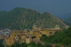 Belle vue de château jaune d'Amber Fort avec les arbres verts, les montagnes et les petites maisons près de Jaipur au Ràjasthàn Photographie stock libre de droits