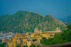 Belle vue de château jaune d'Amber Fort avec les arbres verts, les montagnes et les petites maisons près de Jaipur au Ràjasthàn Photo libre de droits