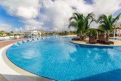 Belle vue de invitation gentille d'une piscine confortable incurvée avec les lits en céramique Images libres de droits