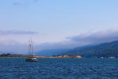 Belle vue de l'océan et des montagnes avec un petit yacht photos stock