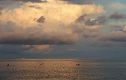 Belle vue de mer avec la formation de bateaux et de nuages de pêche en heures d'or de coucher du soleil, lumière chaude de soirée, Photographie stock