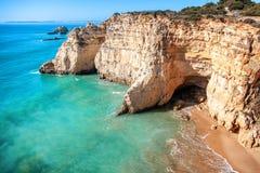 Belle vue de mer avec la plage sablonneuse secrète parmi les roches et la falaise Photographie stock libre de droits