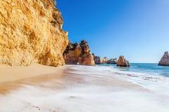 Belle vue de mer avec la plage sablonneuse secrète parmi les roches et la falaise Photo stock