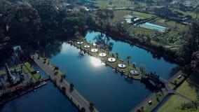 Belle vue du jardin sur l'eau avec un lac, architecture, fontaines, ponts, avenues, gazebos bali Indonésie banque de vidéos