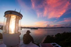 Belle vue supérieure de phare au crépuscule Homme de phare s'asseyant sur la terrasse tout en regardant les nuages fantastiques a images libres de droits