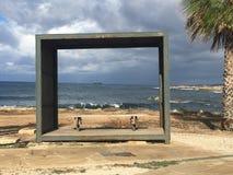 Belle vue sur la mer par le cadre en bois avec des nuages de ciel de paumes photo stock