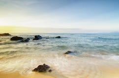 Belle vue tropicale de mer de lever de soleil de plage vague molle frappant la plage sablonneuse Photographie stock