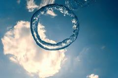 Bellen de ring onderwater stijgt naar de zon stock fotografie