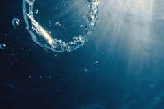 Bellen de ring onderwater stijgt naar de zon stock afbeelding