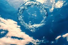 Bellen de ring onderwater stijgt naar de zon stock foto's