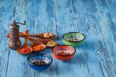 Belles épices colorées dans des cuillères sur une vieille table bleue en bois Images stock