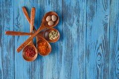 Belles épices colorées dans des cuillères sur une vieille table bleue en bois Photos libres de droits