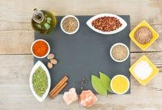 Belles épices colorées dans des cuvettes sur le plateau d'ardoise, l'huile d'olive et le sel L'espace libre pour votre texte Photographie stock libre de droits