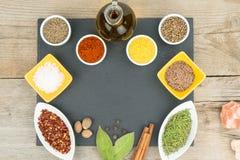 Belles épices colorées dans des cuvettes sur le plateau d'ardoise, l'huile d'olive et le sel L'espace libre pour votre texte Photographie stock