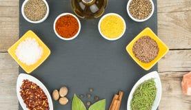 Belles épices colorées dans des cuvettes sur le plateau d'ardoise, l'huile d'olive et le sel L'espace libre pour votre texte Photos stock