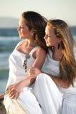 Belles adolescentes au-dessus de mer et de backgr de coucher du soleil Photographie stock