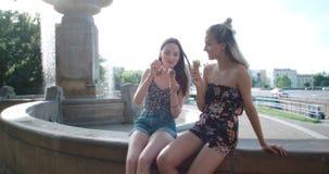 Belles amies ayant l'amusement dans une ville pendant le jour ensoleillé Images libres de droits