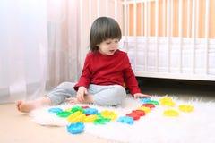Belles 2 années d'enfant en bas âge jouant la mosaïque Images stock