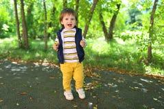 Belles 2 années de garçon d'enfant en bas âge dans des pantalons jaunes dehors Photographie stock libre de droits