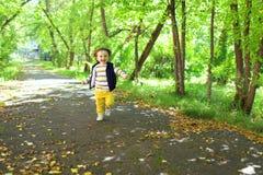 Belles 2 années de garçon d'enfant en bas âge dans des pantalons jaunes fonctionnant en parc Image libre de droits