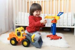 Belles 2 années de garçon d'enfant en bas âge jouant des voitures à la maison Image libre de droits