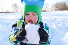 Belles 2 années de garçon d'enfant en bas âge mangeant la neige Image libre de droits